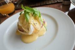 Ägg Benedict består av en engelsk muffin som överträffas med skinka eller bacon, ett tjuvjagat ägg och hollandaisesås på en vit p Arkivbild