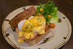 Ägg Benedict med helt veterostat bröd, tjuvjagade ägg, Hoallandaise sås, skinka och ny sallad på en cirkelplatta Royaltyfria Foton