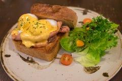 Ägg Benedict med helt veterostat bröd, tjuvjagade ägg, Hoallandaise sås, skinka och ny sallad på en cirkelplatta Royaltyfri Fotografi