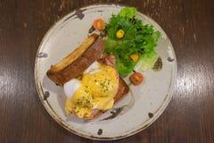 Ägg Benedict med helt veterostat bröd, tjuvjagade ägg, Hoallandaise sås, skinka och ny sallad på en cirkelplatta Arkivbild