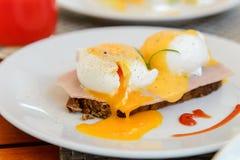Ägg benedict på den vita maträtten på frukosten - tjuvjagat ägg på skinkasli Royaltyfria Bilder