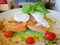 Ägg Benedict på rostat bröd med bacon, raketsallad, avokadosås och tomaten Royaltyfri Fotografi
