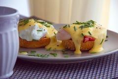 Ägg Benedict rostade muffin, skinka, tjuvjagade ägg och läcker buttery hollandaisesås Arkivfoto