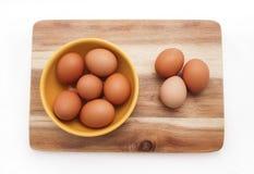 Ägg bruna ägg i gul platta på träbrädet, bästa sikt Arkivfoton