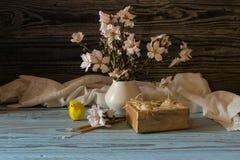 Ägg, en bukett av mandelfilialer och kyrkastearinljus Royaltyfria Foton