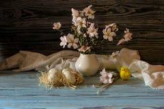 Ägg, en bukett av mandelfilialer och kyrkastearinljus Royaltyfria Bilder