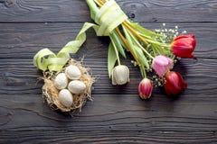 Ägg, en bukett av tulpan och kyrkastearinljus Royaltyfria Bilder