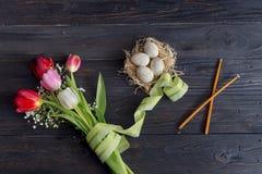 Ägg, en bukett av tulpan och kyrkastearinljus Fotografering för Bildbyråer