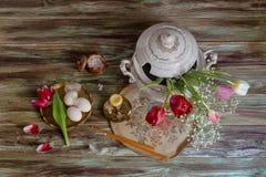Ägg, en bukett av tulpan, rökelse och kyrkastearinljus Royaltyfri Foto