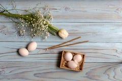 Ägg, en vit tulpan och kyrkastearinljus Fotografering för Bildbyråer