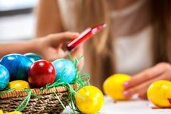 Ägg för barnmålarfärgpåsk hemma Arkivfoto