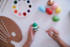 Ägg för kvinnamålningpåsk hemma förbereda sig för easter familj arkivbild