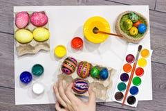 Ägg för kvinnamålningpåsk lyckliga easter Arkivfoto