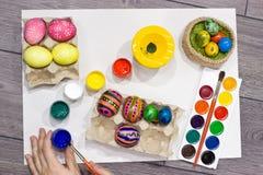 Ägg för kvinnamålningpåsk lyckliga easter Arkivfoton