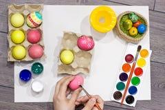 Ägg för kvinnamålningpåsk lyckliga easter Arkivbild