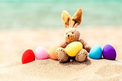 Ägg för påskkanin och färgpå den sandiga stranden förbi royaltyfria foton