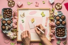 Ägg för påsksammansättningschoklad, vårblommor, olika garneringar, träkaniner och fåglar, flicka undertecknar en vykort, bästa v Arkivbild