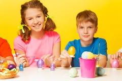 Ägg för pojke- och flickamålningpåsk på tabellen Fotografering för Bildbyråer