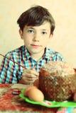 Ägg för pojkeeaster målarfärg och dekorerar kakan arkivfoton