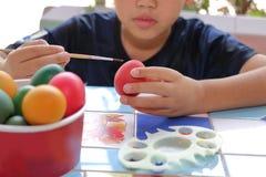 Ägg för pysmålningpåsk med målarpenseln Royaltyfria Bilder