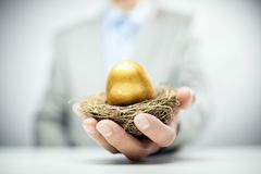 Ägg för rede för avgångbesparingar guld- i affärsmanhand fotografering för bildbyråer