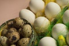 Ägg för för vithönahöna och vaktel i den kulöra pappers- eco-vänskapsmatchen som förpackar med bakgrund för påsk för sisalhampanä Arkivfoton