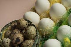 Ägg för för vithönahöna och vaktel i den kulöra pappers- eco-vänskapsmatchen som förpackar med bakgrund för påsk för sisalhampanä Arkivbild