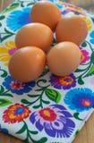 Ägg från organiskt lantbruk från byn som ordnas på en färgrik bordduk i folk modeller royaltyfri fotografi