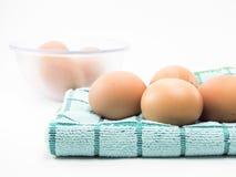 Ägg fyra på tyg och ägg i den isolerade klara koppen Arkivfoto