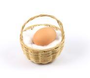 Ägg i bambukorg med vit bomull Arkivfoton