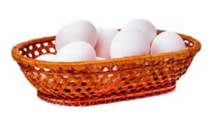 Ägg i bambukorg på en vit bakgrund Fotografering för Bildbyråer