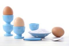 Ägg i blåa äggkoppar Fotografering för Bildbyråer