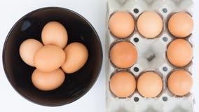 Ägg i bunke och i magasin Arkivfoto