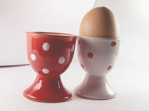 Ägg i den vita äggkoppen med den röda äggkoppen Arkivbilder