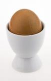 Ägg i den vita äggkoppen, på vit Arkivbilder