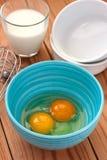 Ägg i en blå bunke och ett exponeringsglas av mjölkar Royaltyfria Bilder