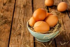 Ägg i en blå bunke på lantligt tappningträ Fotografering för Bildbyråer