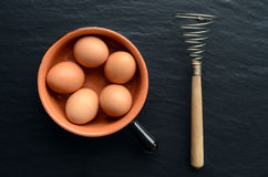 Ägg i en bunke med eggbeateren Arkivbilder