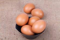 Ägg i en bunke på den bruna säcken Arkivfoton
