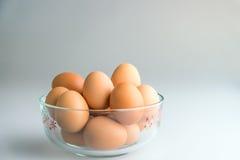 Ägg i en bunke på en vit bakgrund Royaltyfri Foto