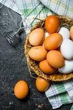 Ägg i en korg med viftar och servetten royaltyfri bild
