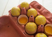 Ägg i en packe på en träbakgrund, isolat Gulingmodeller målas Royaltyfri Foto