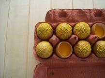 Ägg i en packe på en träbakgrund, isolat Gulingmodeller målas Royaltyfria Foton