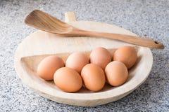 Ägg i en träplatta arkivfoton