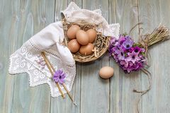 Ägg i en vide- korg, en bukett av lösa anemoner och kyrkastearinljus Royaltyfri Bild
