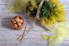 Ägg i en vide- korg, en bukett av mimosan och kyrkastearinljus Royaltyfri Foto