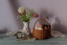 Ägg i en vide- korg, en bukett av tulpan, symbol och kyrkastearinljus Royaltyfria Foton