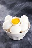 Ägg i en vit bunke, äggula i ett skal Arkivfoton