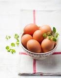 Ägg i en vit bunke på beige servett Arkivfoton