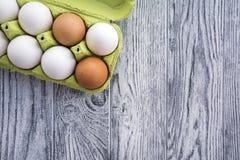 Ägg i ett magasin och en träbakgrund, bästa sikt Royaltyfri Bild